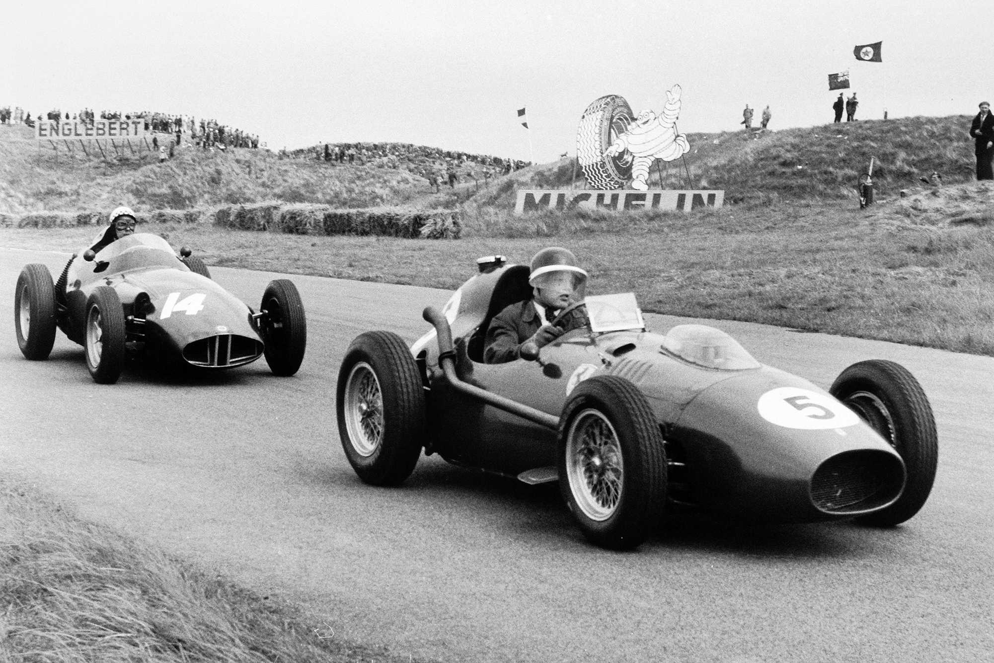 Mike Hawthorn driving the Ferrari Dino 246 in 5th position, leads Jean Behra, BRM P25 in 3rd position