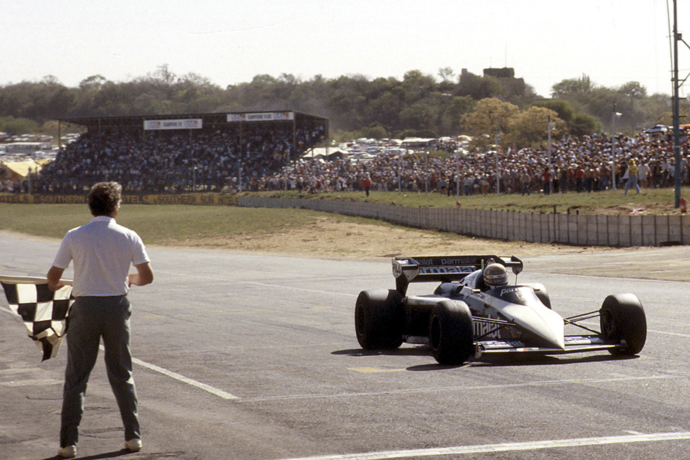 Riccardo Patrese takes the chequered flag.
