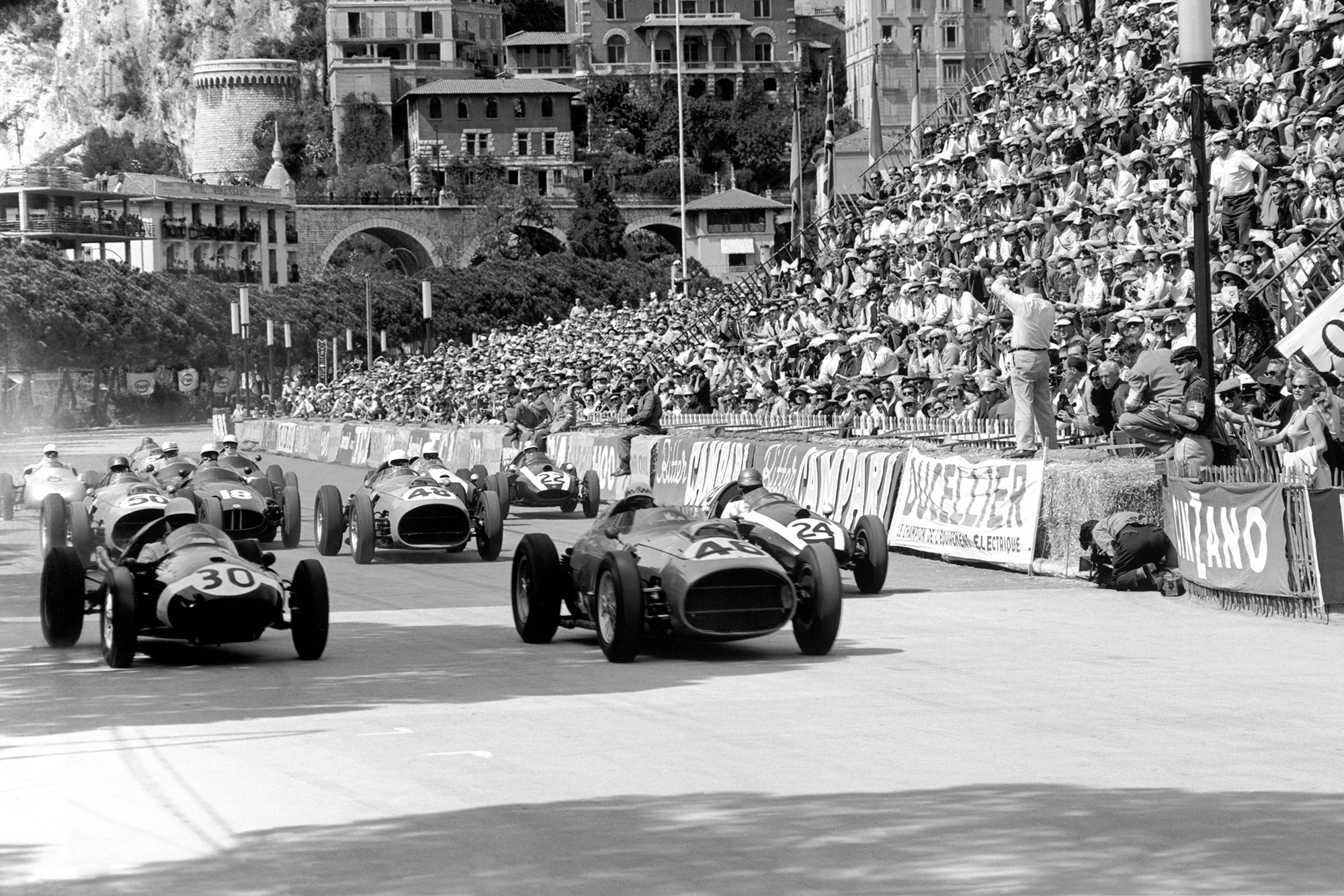 The race starts, with Stirling Moss, number 30 Cooper T51-Climax, and Jean Behra, number 46 Ferrari Dino 246, Tony Brooks in number 50 Ferrari Dino 246, Jo Bonnier, number 18 BRM P25, Phil Hill in number 48 Ferrari Dino 246, and Jack Brabham, number 24 Cooper T51-Climax.