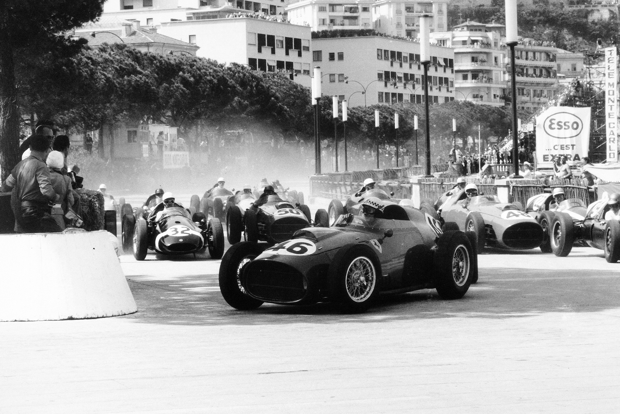 Jean Behra driving a Ferrari Dino 246, leads Stirling Moss in his Cooper T51-Climax and Jack Brabham driving Cooper T51-Climax at the start of the race.