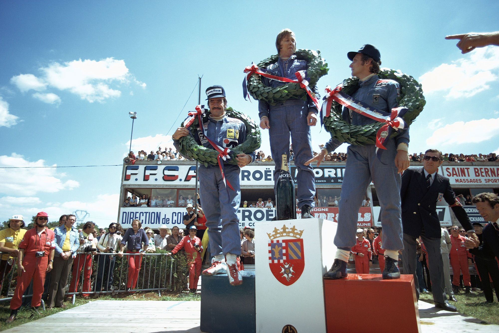 Ronnie Peterson stands on the top step of the podium after winning the 1974 French Grand Prix, Paul Ricard.