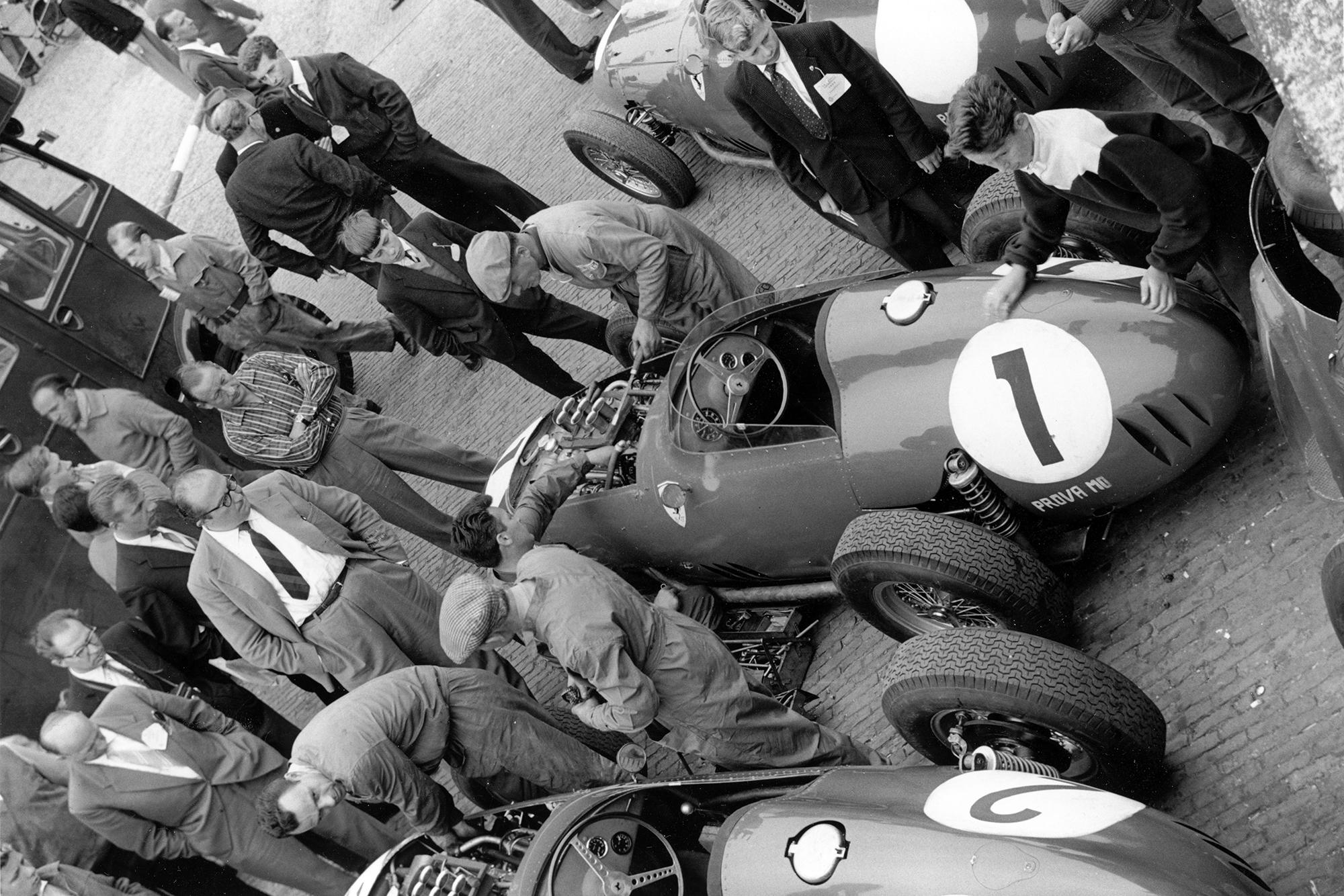 In the paddock Carlo Chiti (glasses, centre) overseas mechanics working on the Ferrari Dino 246 of Jean Behra.