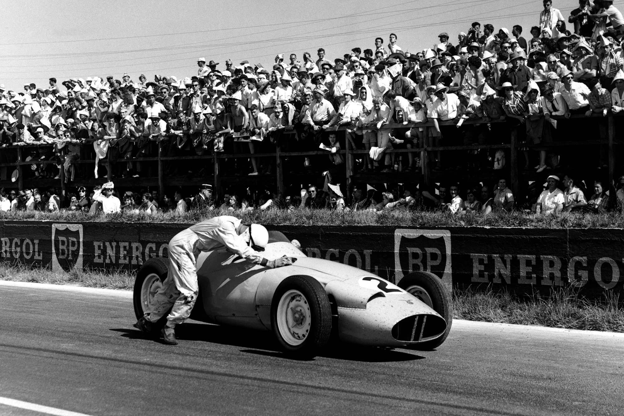 Stirling Moss pushes his BRM P25 , but is later disqualified for receiving outside assistance.