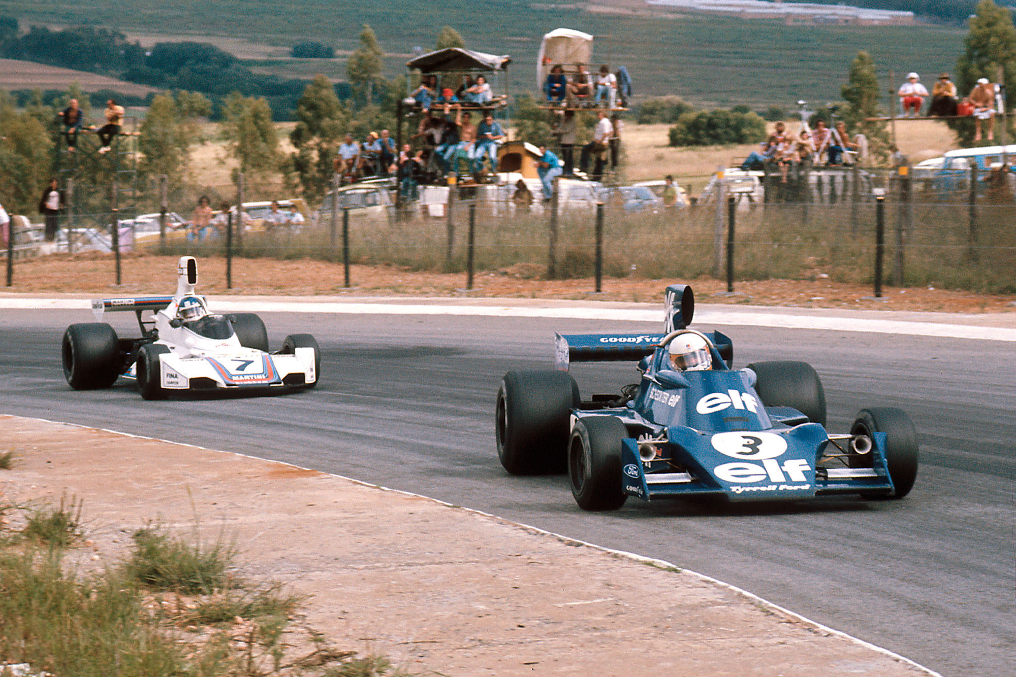 Jody Scheckter (Tyrrell) is chased By Carlos Pace (Brabham) at the 1975 South African Grand Prix, Kyalami.