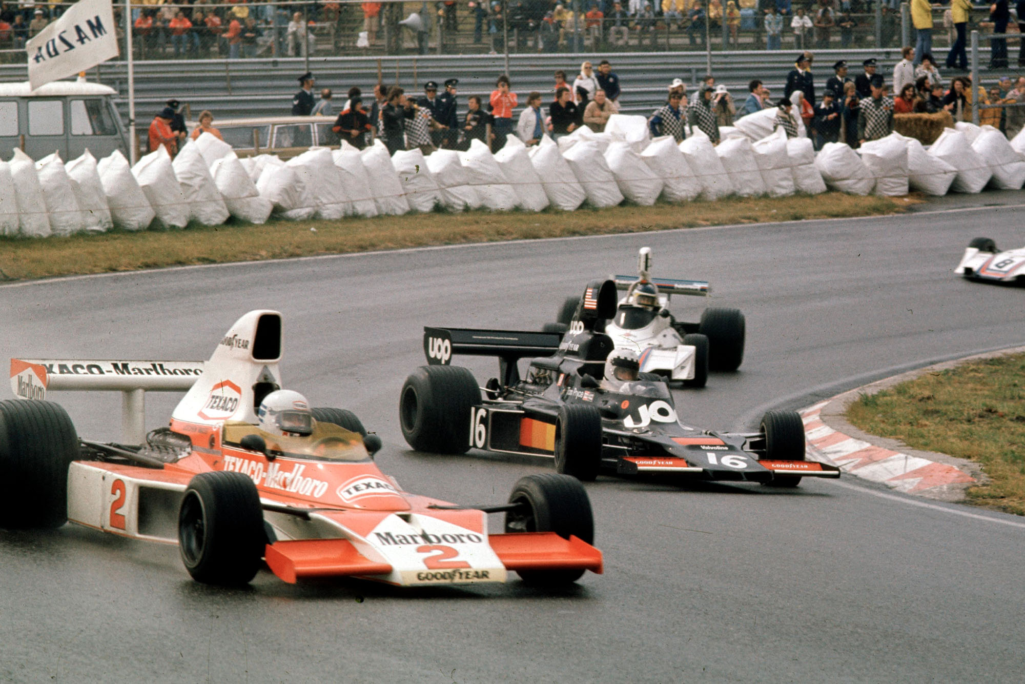 Jochen Mass (McLaren, foreground) and Tom Pryce (Shadow) attempt to get to grips with the slippery conditions at the 1975 Dutch Grand Prix, Zandvoort.