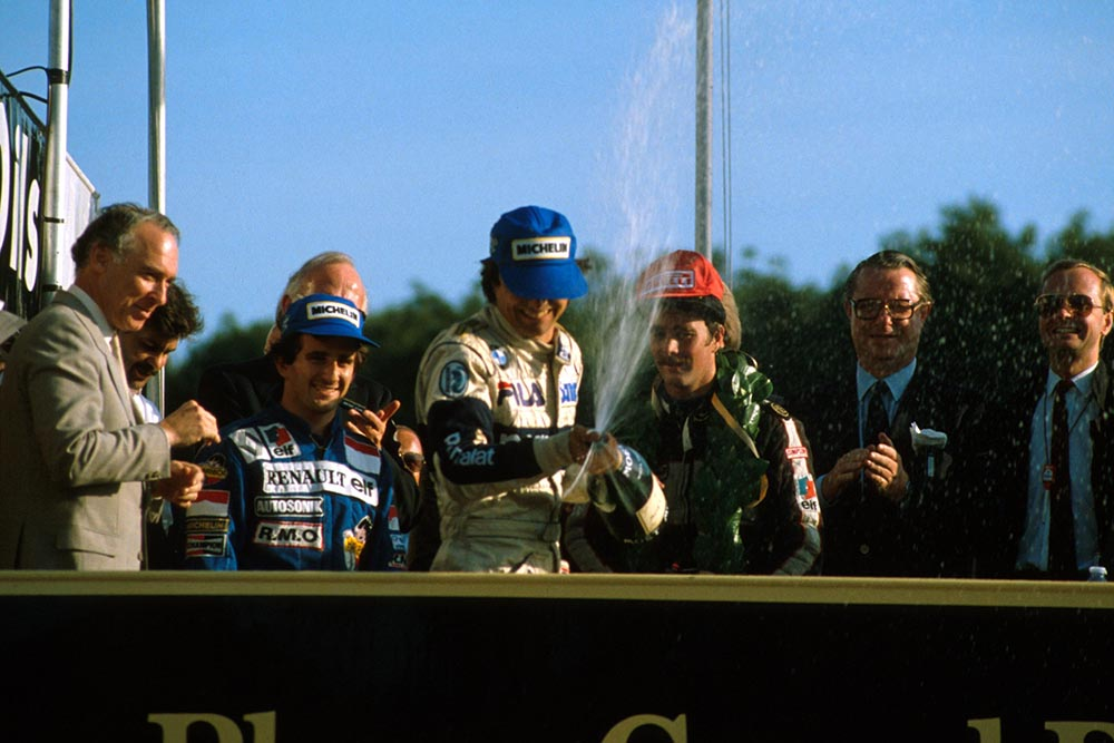 Winner Nelson Piquet sprays the champagne as 2nd place Alain Prost left, and Nigel Mansell, right look on.