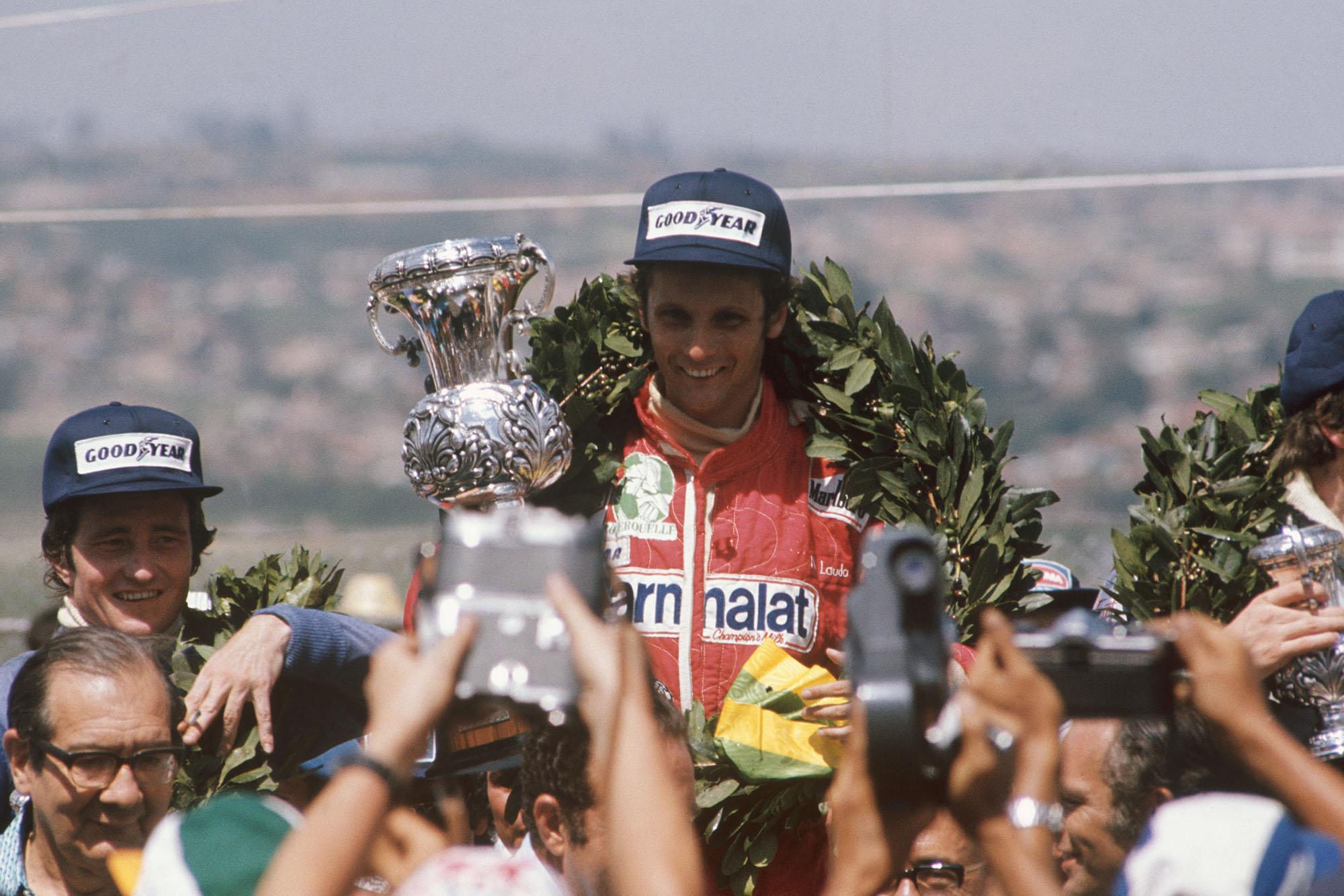 Niki Lauda stands atop the podium after winning the 1976 Brazilian Grand Prix