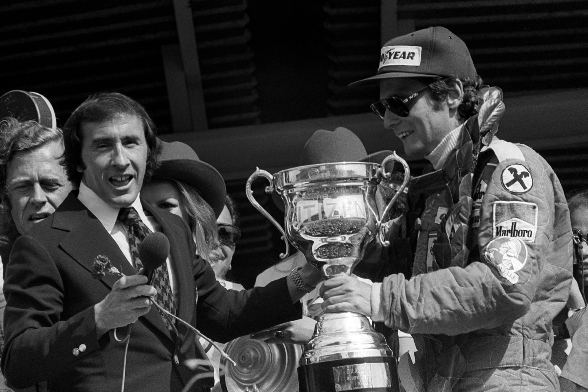 Niki Lauda (Ferrari) is handed the trophy by Jackie Stewart at the 1976 South African Grand Prix.