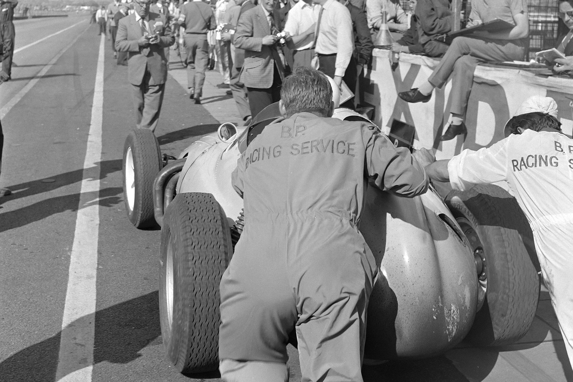 Stirling Moss is pushed out of the pit lane in his BRM P25.