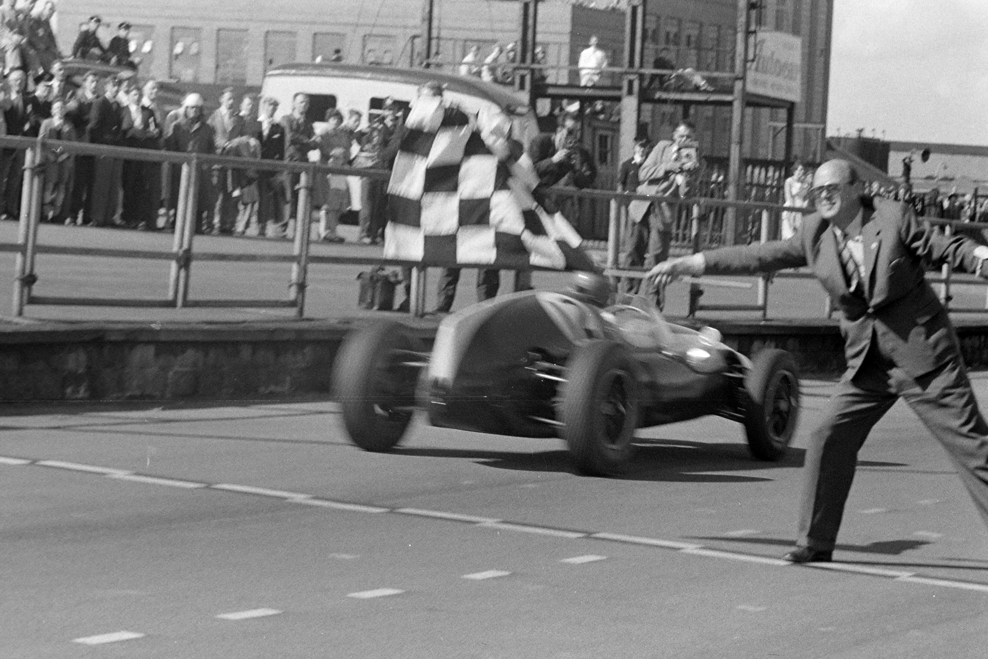 Jack Brabham, Cooper T51 Climax, takes the chequered flag for victory.