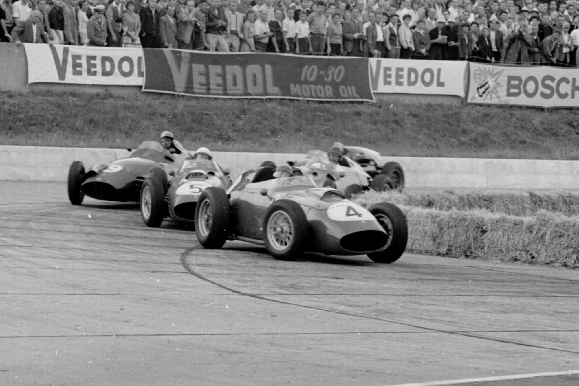 Stirling Moss leads Maurice Trintignant both in Cooper T51 Climaxs and Carroll Shelby in an Aston Martin DBR4/250 into the hairpin.