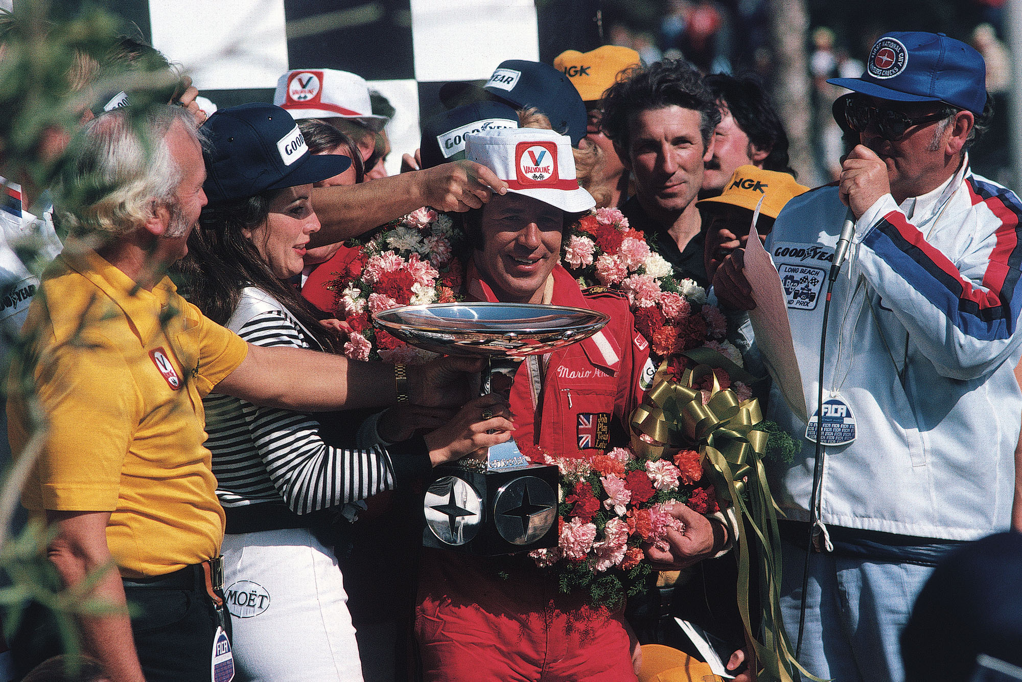 Mario Andretti (Lotus) celebrates on the podium after winning the 1977 United States Grand Prix West, Long Beach.