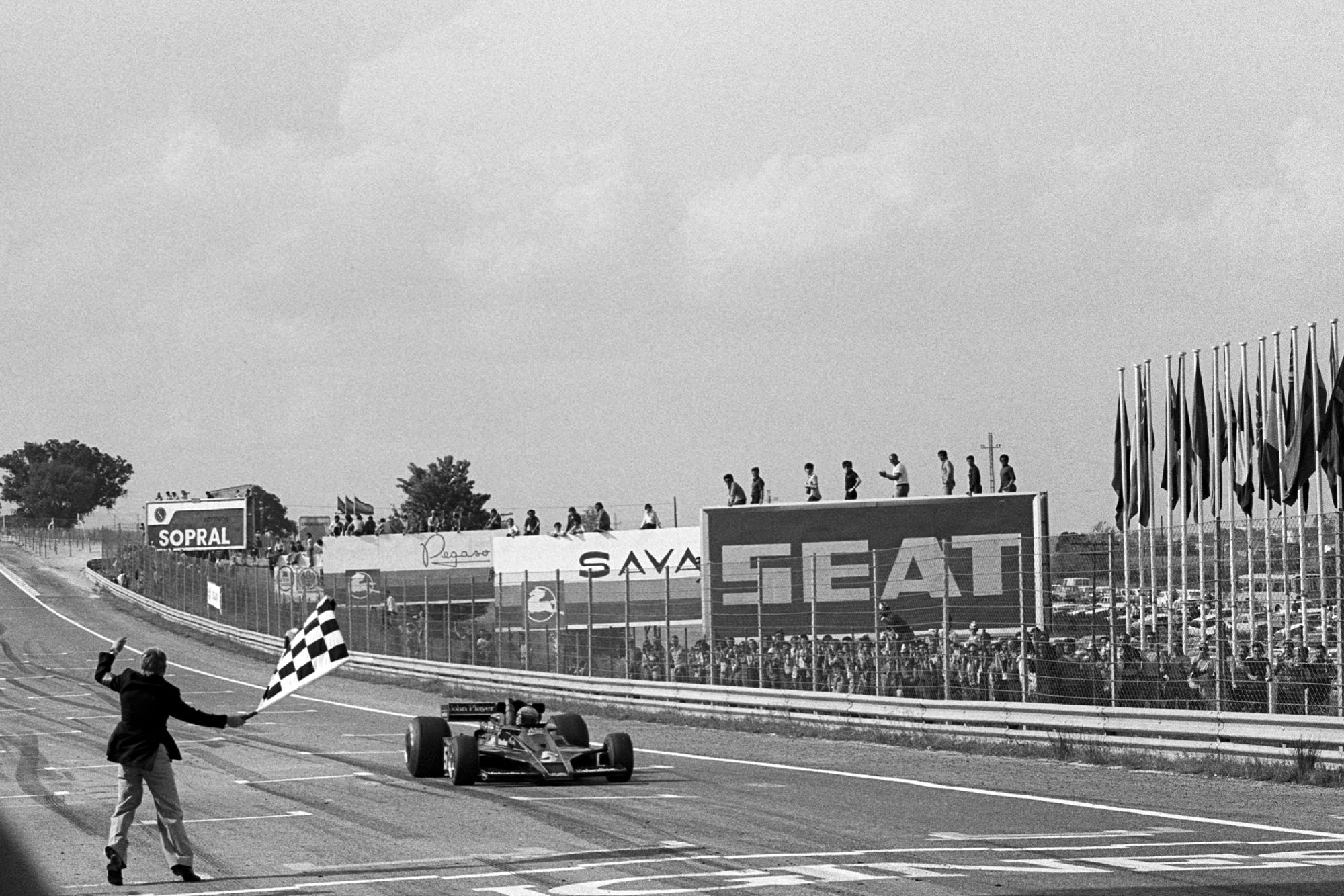 Mario Andretti takes the chequered flag ta the 1977 Spanish Grand Prix, Jarama.