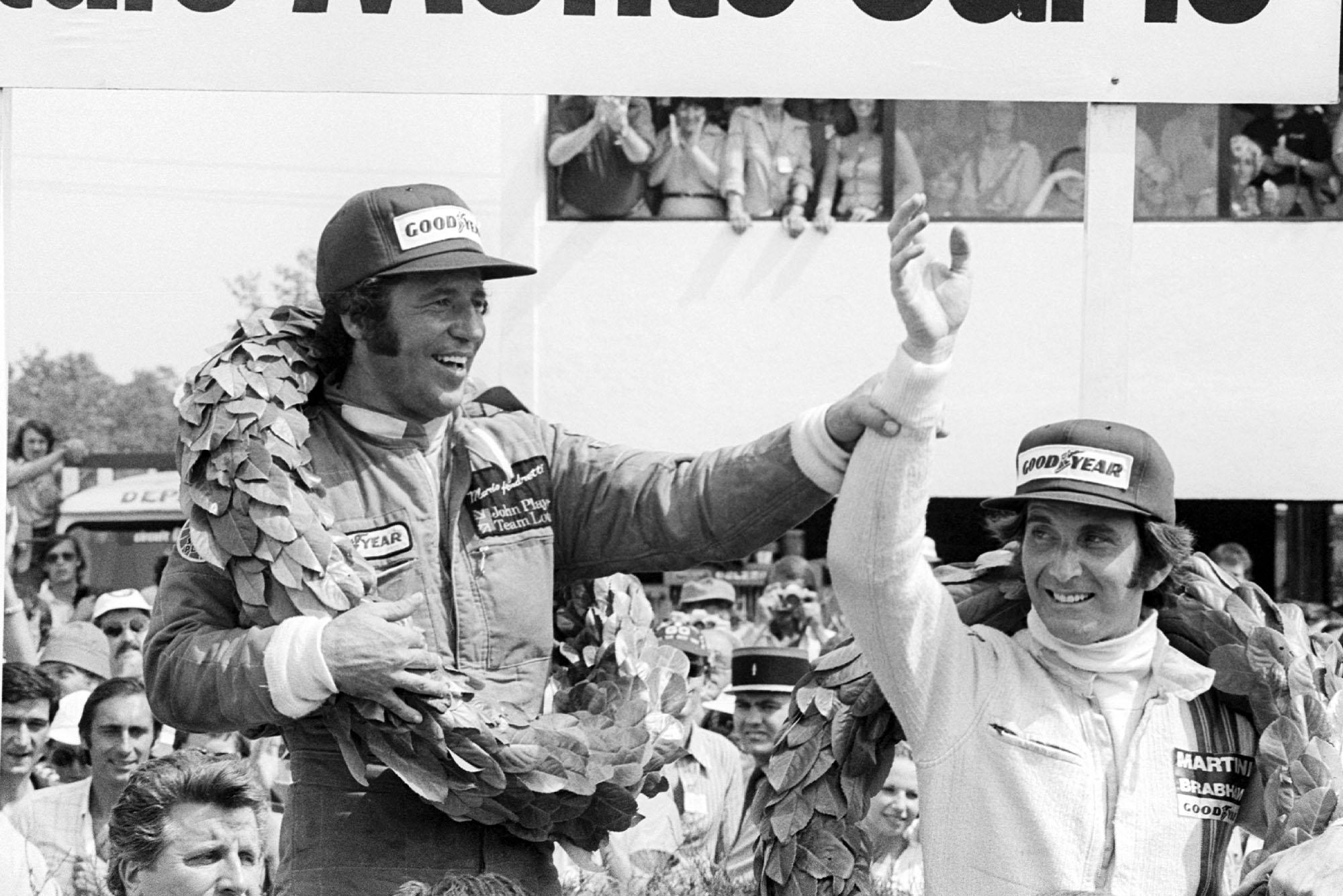 Mario Andretti (Lotus) celebrates on the podium after winning the 1977 French Grand Prix, Dijon.