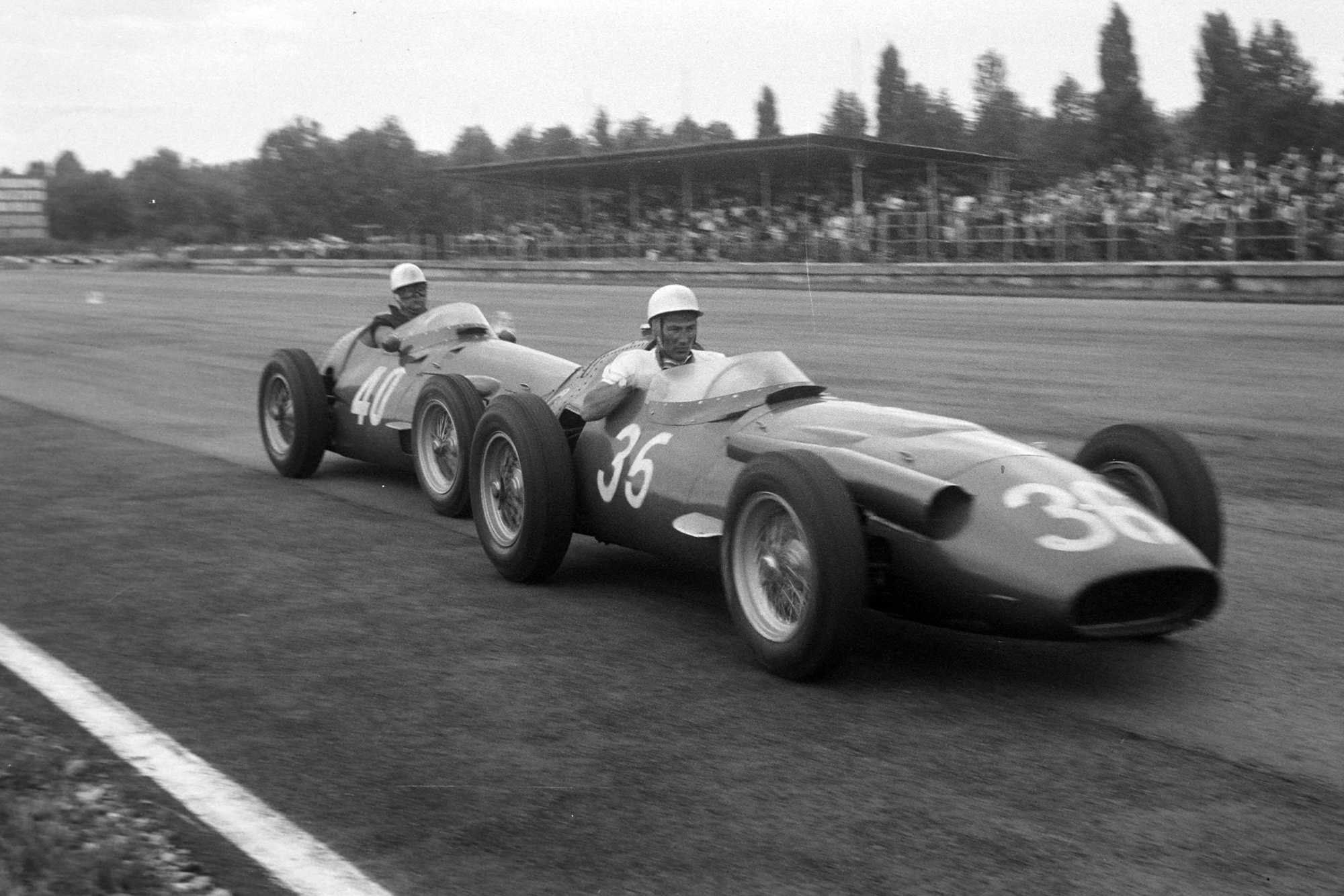 Stirling Moss whose Maserati 250F has run out of fuel, recieves a push back to the pits from team-mate Luigi Piotti, 1956 Italian Grand Prix, Monza.