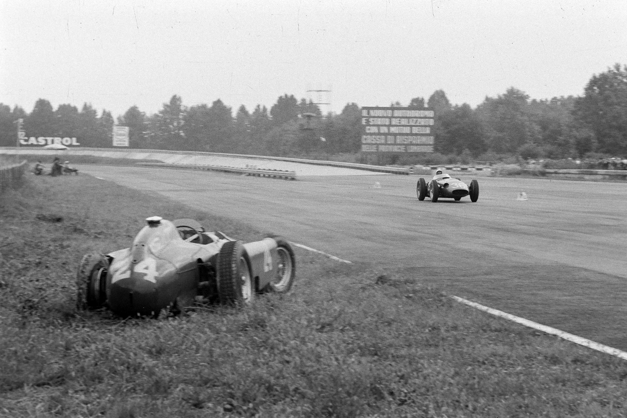 Stirling Moss, Maserati 250F, passes the abandoned Ferrari D50 of Eugenio Castellotti, 1956 Italian Grand Prix, Monza.