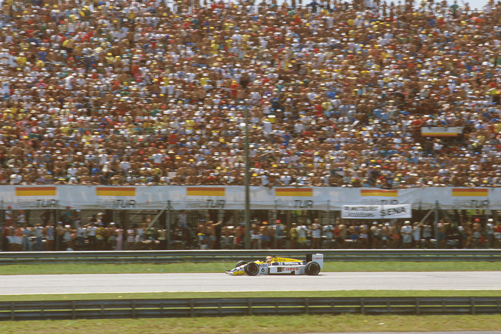 Nelson Piquet (Williams FW11 Honda)passes a packed grandstand.