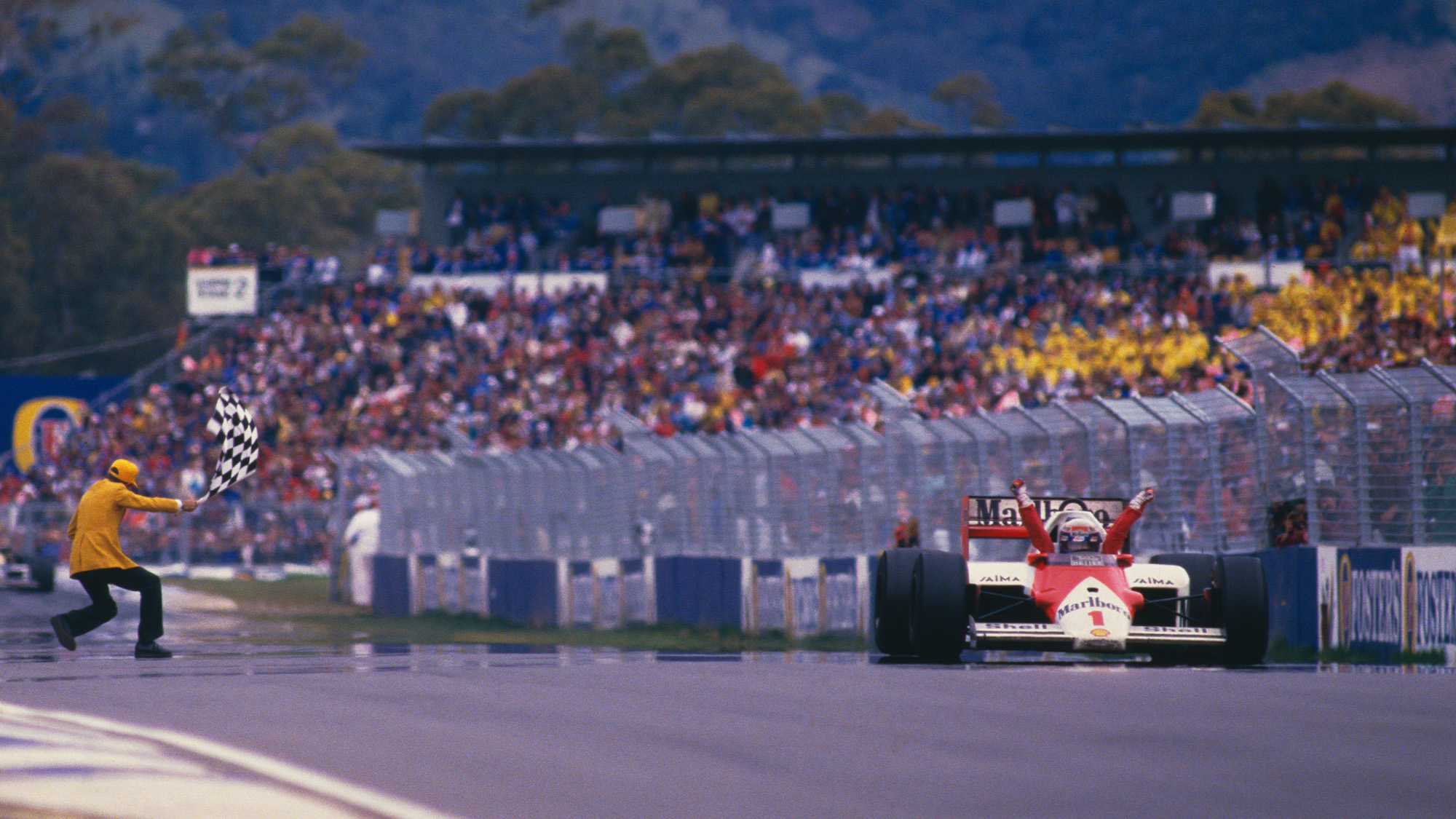 Alain Prost raises his arms in the air as he crosses the finish line at Adelaide to win the Australian Grand Prix and 1986 world championship
