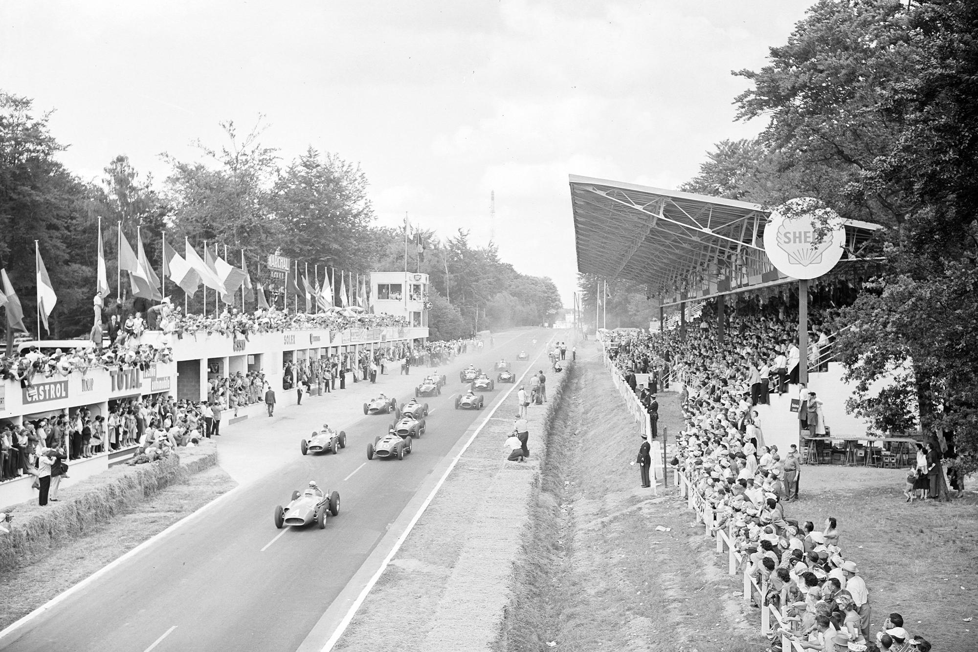 Jean Behra, Maserati 250F, leads Luigi Musso, Ferrari D50 (#10), Juan Manuel Fangio, Maserati 250F (#2), and Peter Collins, Ferrari D50 (#12), at the start of the 1957 French Grand Prix.