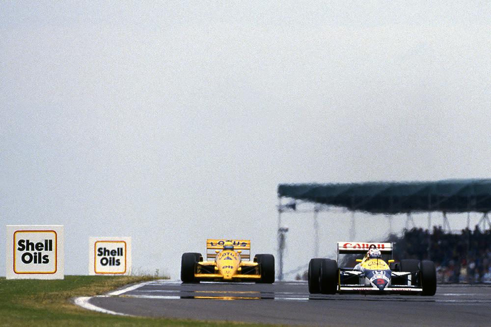 Nigel Mansell, Williams FW11B, leads Ayrton Senna, Lotus 99T.