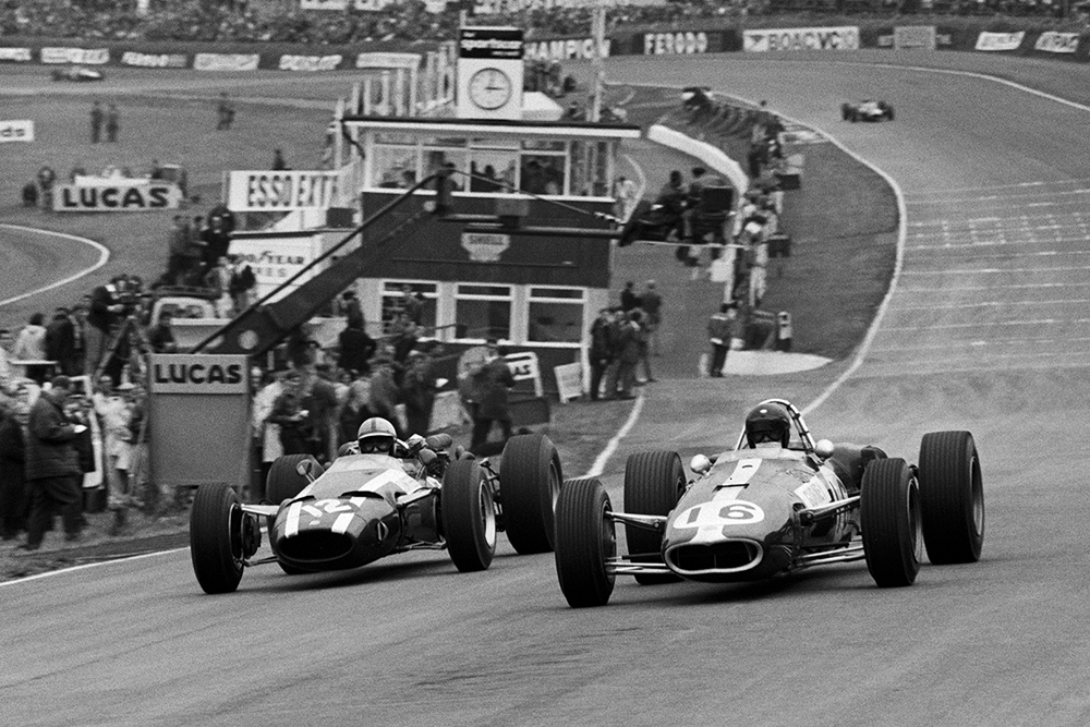 (L to R): Race retiree John Surtees in a Cooper T81 moves to pass fellow retiree Dan Gurney in his Eagle T1G under braking into Paddock Hill Bend.