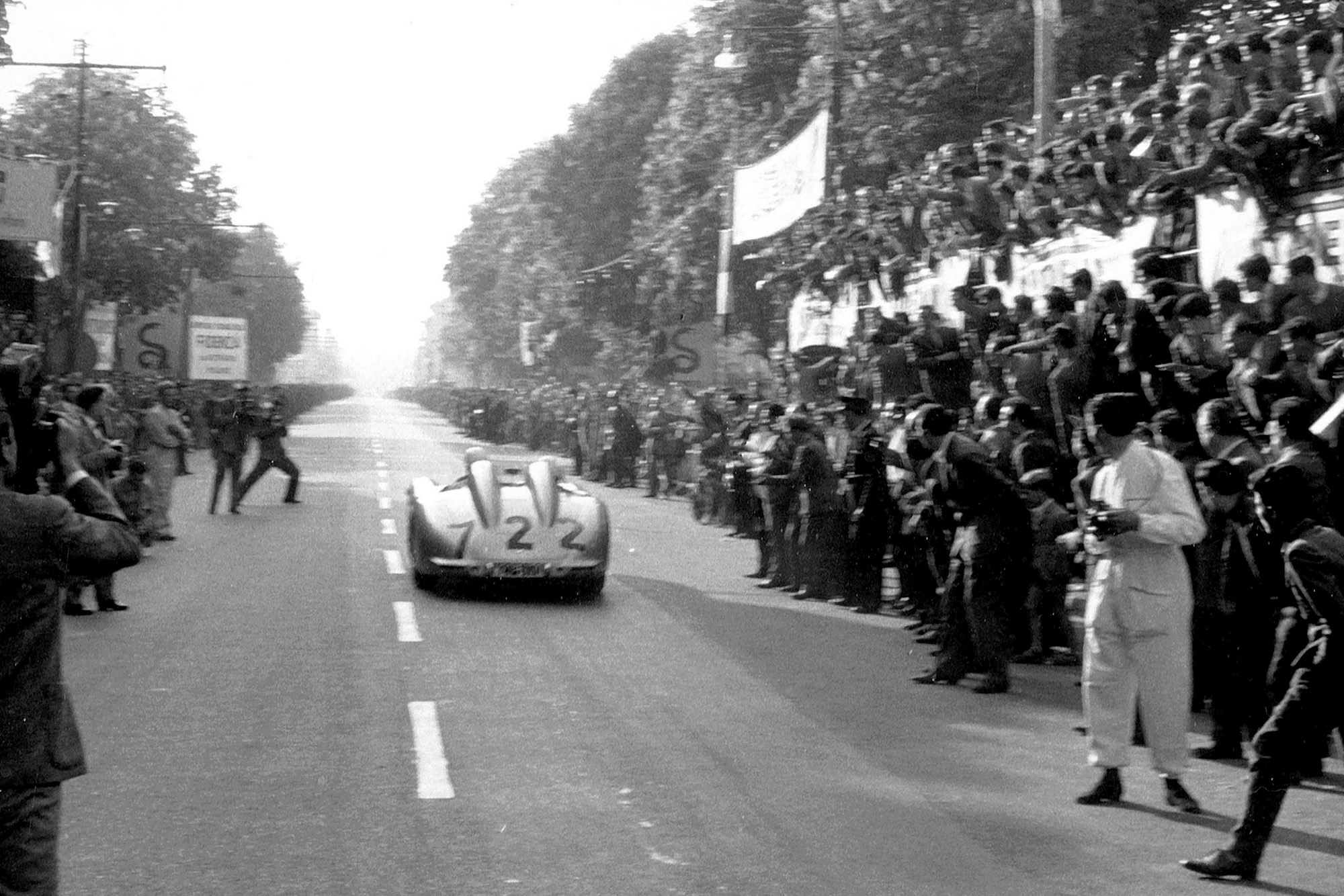 The Moss-Jenkinson Mercedes races past spectators at 1955 Mille Miglia Italy