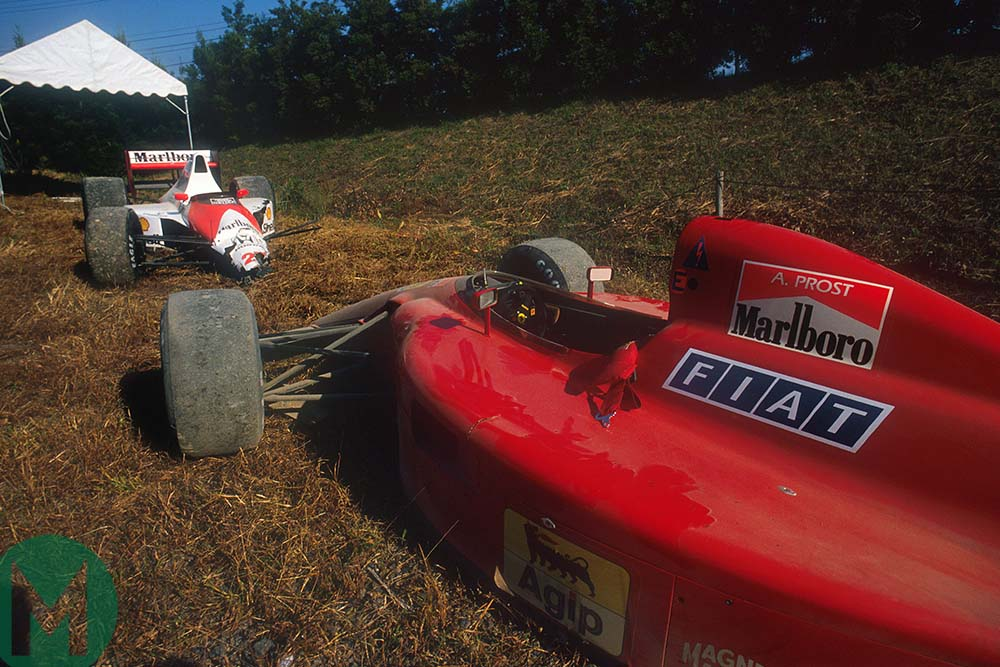 The damaged McLaren and Ferrari cars are parked by the side of the Suzuka track Japanese Grand Prix 1990