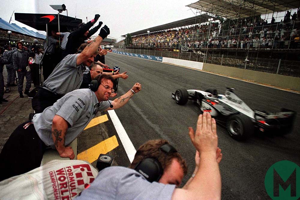 Mika Hakkinen wins the 1998 Brazilian Grand Prix for McLaren-Mercedes, his team celebrating on the pitwall