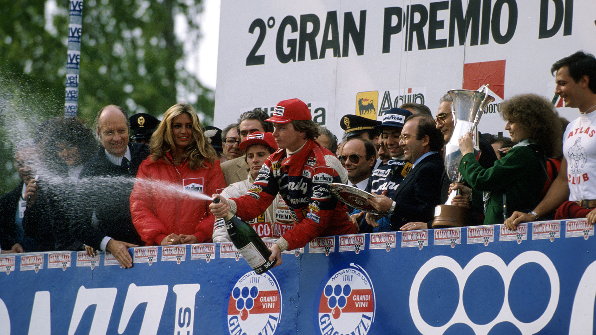 Didier Pironi sprays champagne on the podium at Imola while Gilles Villeneuve watches on after the 1982 San Marino Grand Prix
