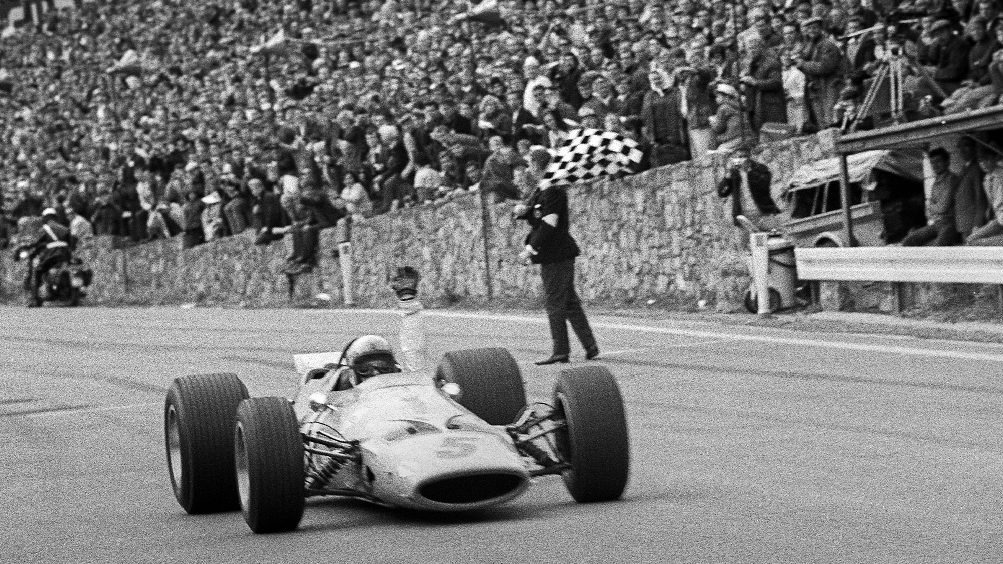 Bruce McLaren crosses the line at Spa Francorchamps to win the 1968 F1 Belgian Grand prix