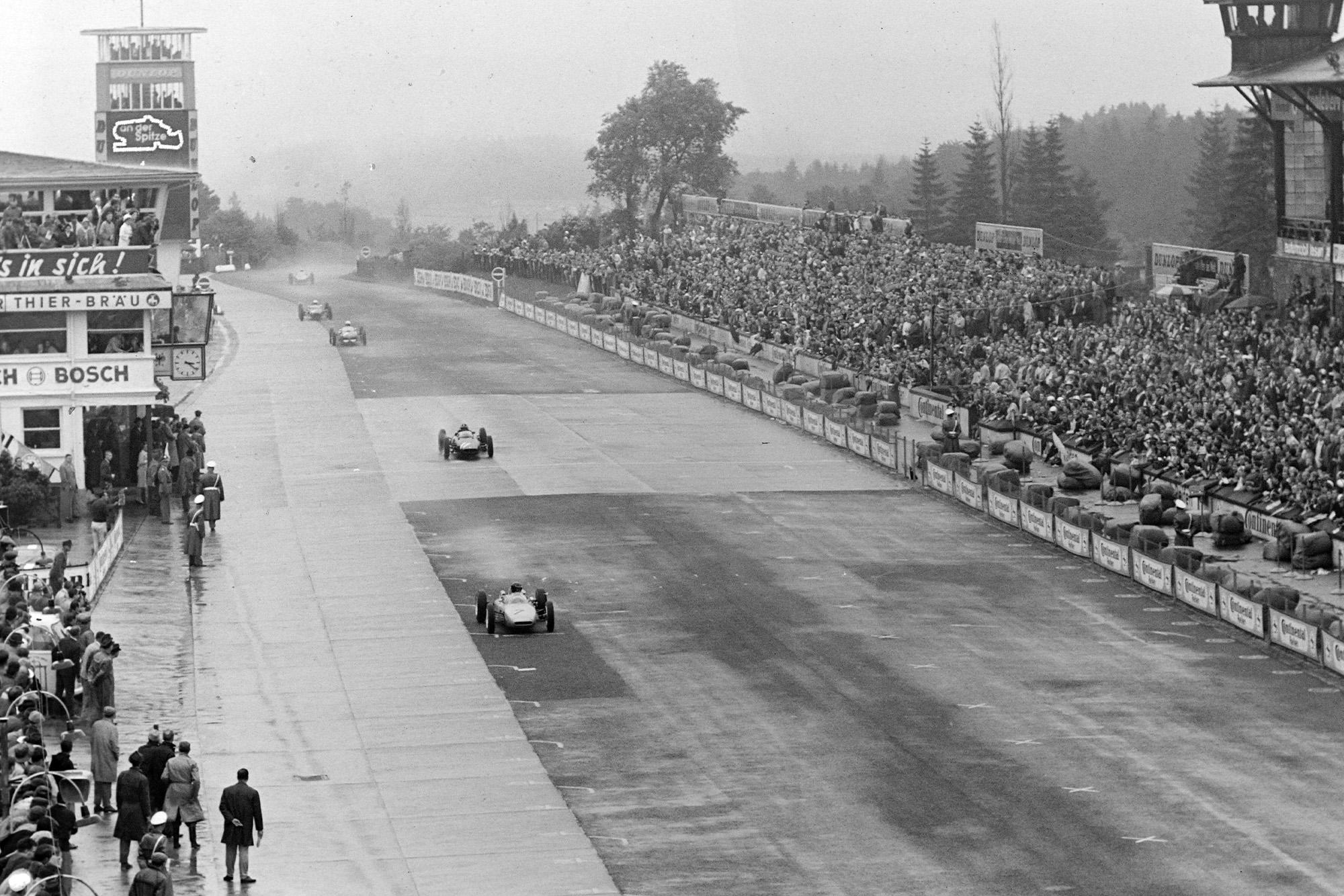 Dan Gurney leads Graham Hill on the pit straight
