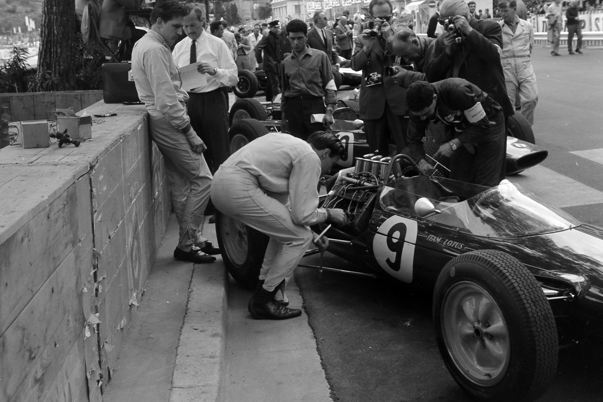 Jim Clark works on his Lotus 25 Climax in the pits