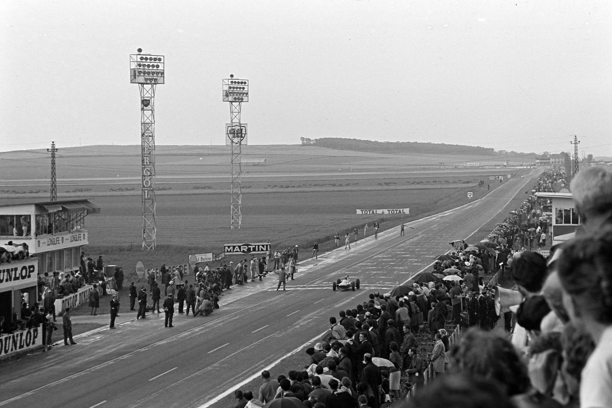 Jim Clark, Lotus 25 Climax, crosses the finish line and takes the chequered flag.