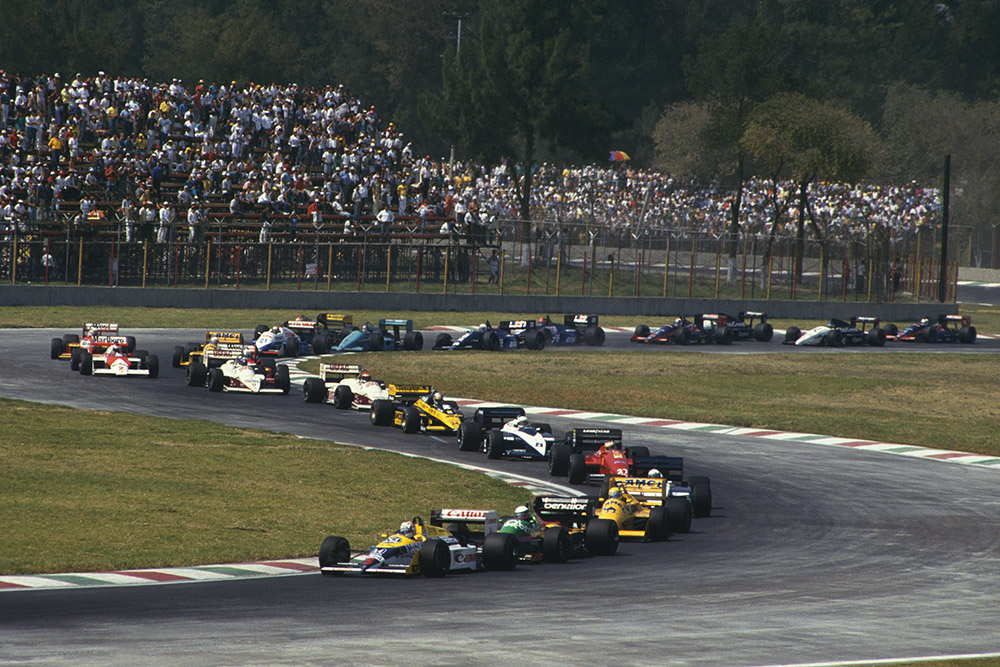 Nigel Mansell (Williams FW11B Honda) 1st position, leads Teo Fabi (Benetton B187 Ford), Ayrton Senna (Lotus 99T Honda) and the rest of the field on the first lap of the Mexican GP.