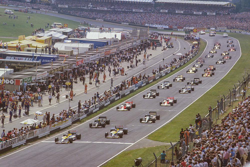 Nelson Piquet leads away from Nigel Mansell (both Williams FW11 Honda's), Ayrton Senna (Lotus 98T Renault) and Gerhard Berger (Benetton B186 BMW) at the start.