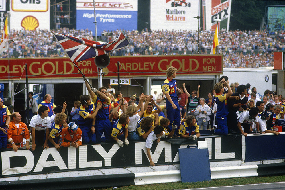 Williams team on the pit wall cheering home Nigel Mansell to 1st place.