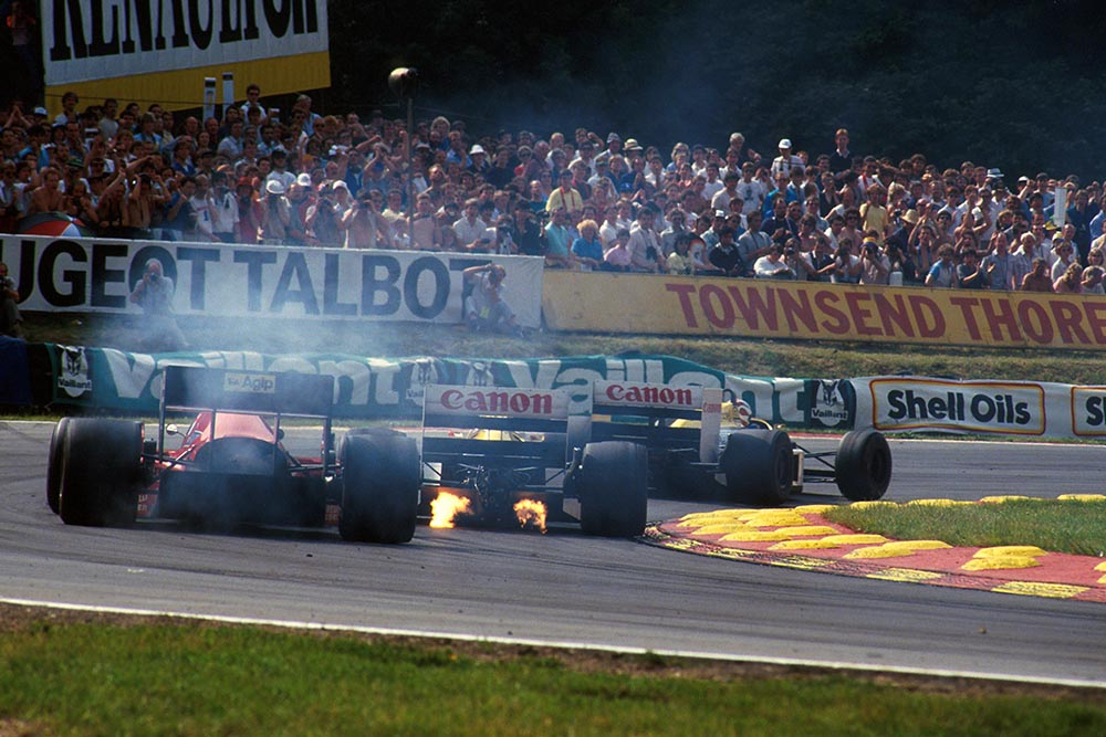 The flame spitting Williams FW11 of Nigel Mansell leads the smoking Ferrari F186.
