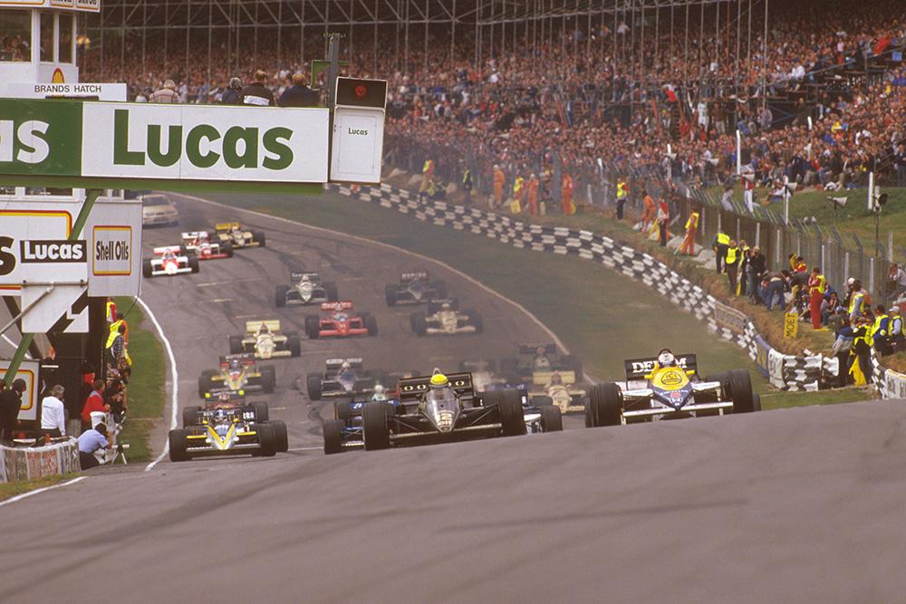 Ayrton Senna (Lotus 97T Renault) leads Nigel Mansell (Williams FW10 Honda) on the climb upto Paddock Hill Bend at the start.