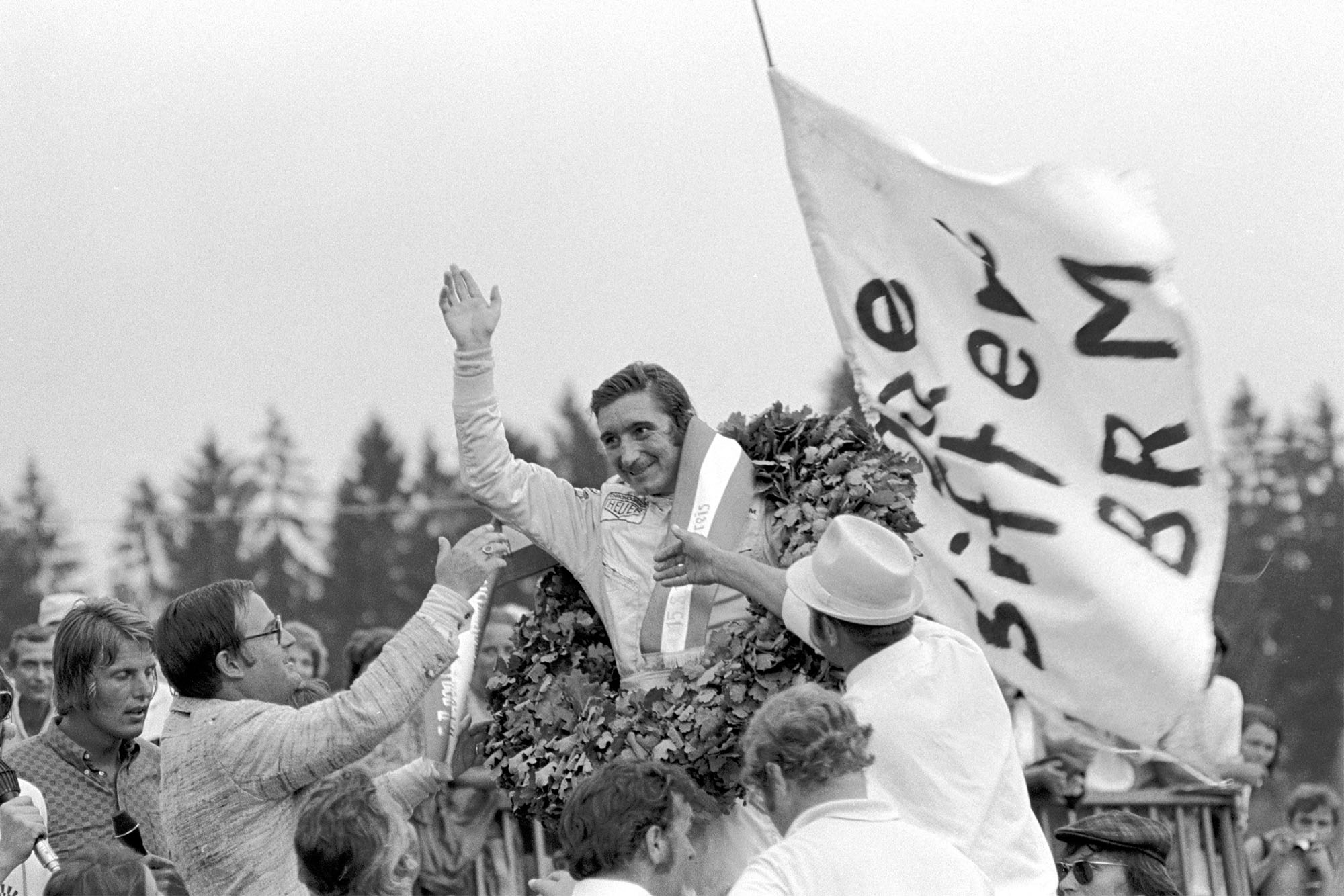 Jo Siffert waves to crowds from the podium after winning the 1971 French Grand Prix.