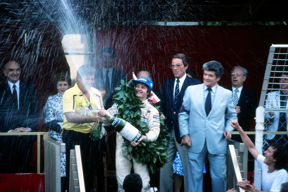 Race winner Gilles Villeneuve sprays the victory champagne on the podium.