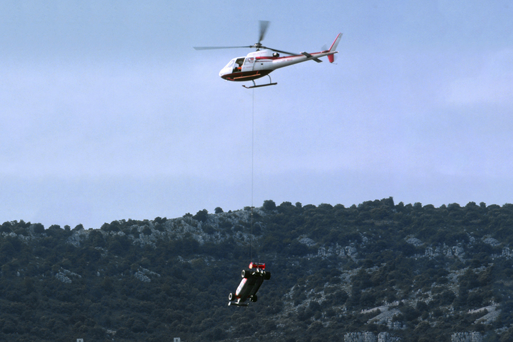 The Alfa Romeo 179C of Mario Andretti is lifted off the circuit by helicopter.