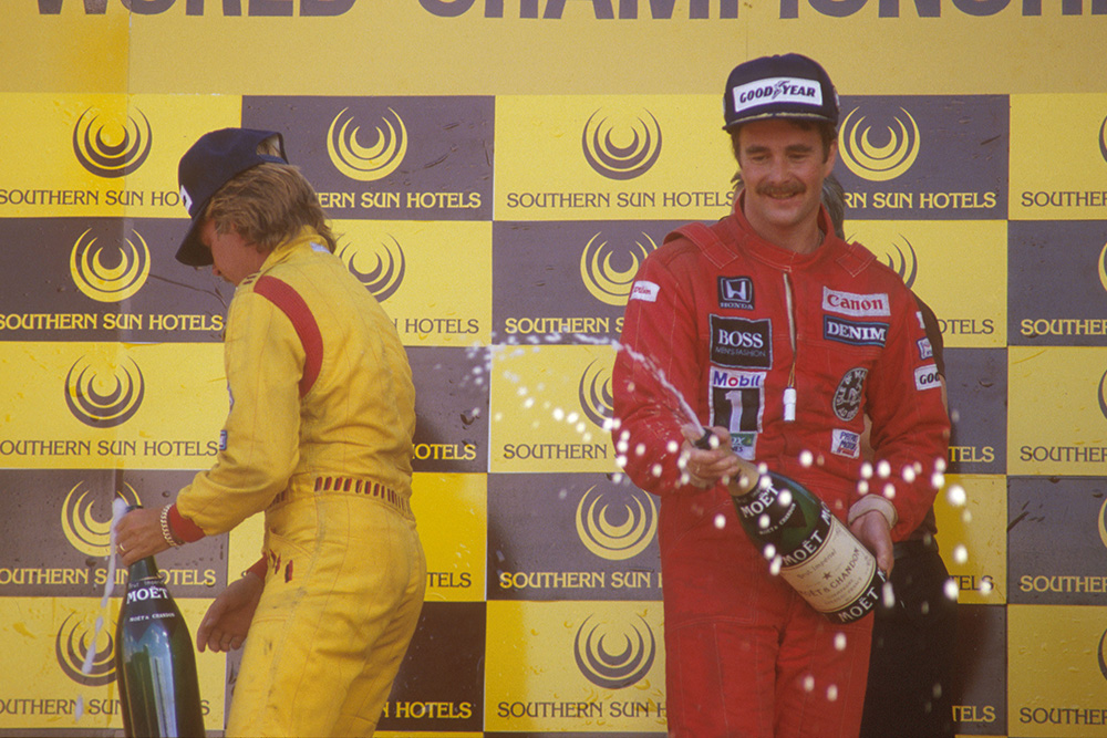 Nigel Mansell, 1st position and teammate Keke Rosberg, 2nd position celebrate on the podium.