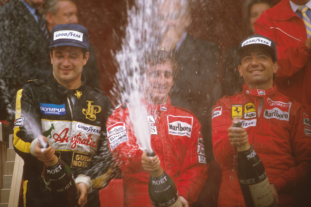 Alain Prost, 1st position, Elio de Angelis, 2nd position and Michele Alboreto, 3rd position on the podium.