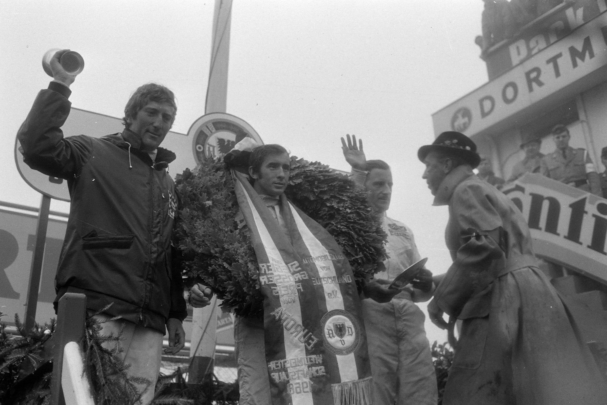 ackie Stewart, 1st position, celebrates victory on the podium with Graham Hill, 2nd position, and Jochen Rindt, 3rd position.