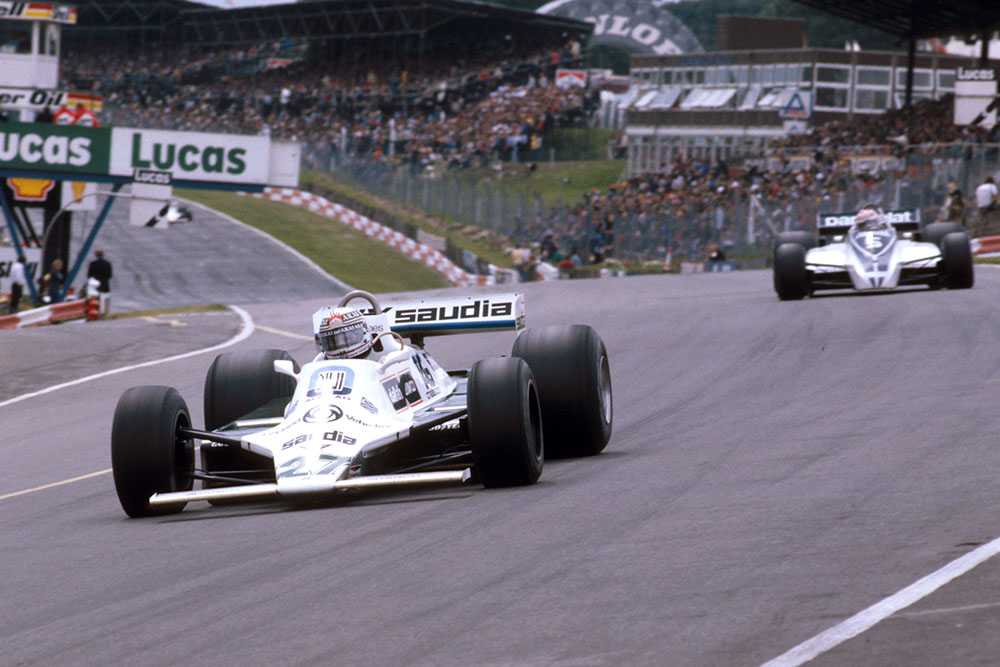 Alan Jones (Williams FW07B Ford) at Paddock Hill Bend, with Nelson Piquet (Brabham BT49 Ford) behind.