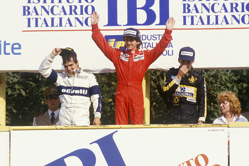 Alain Prost, 1st position, celebrates with Nelson Piquet, 2nd position and Ayrton Senna, 3rd position, on the podium.