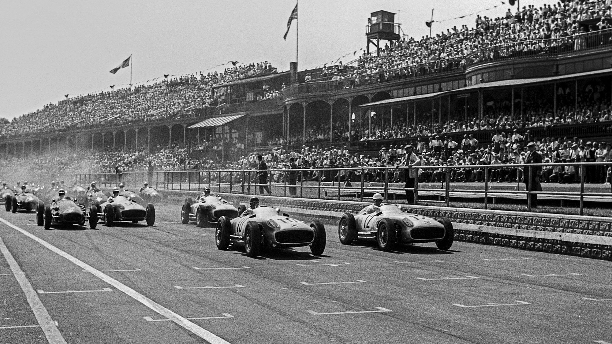Juan Manuel Fangio and Stirling Moss lead at the start of the 1955 British Grand Prix at Aintree