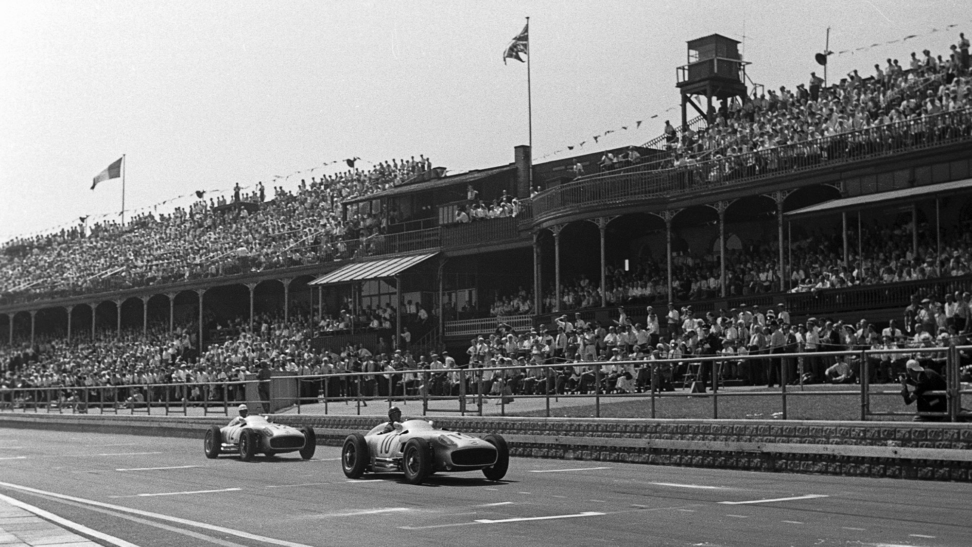 Juan Manuel Fangio leads across the start finish line at Aintree during the 1955 British Grand Prix