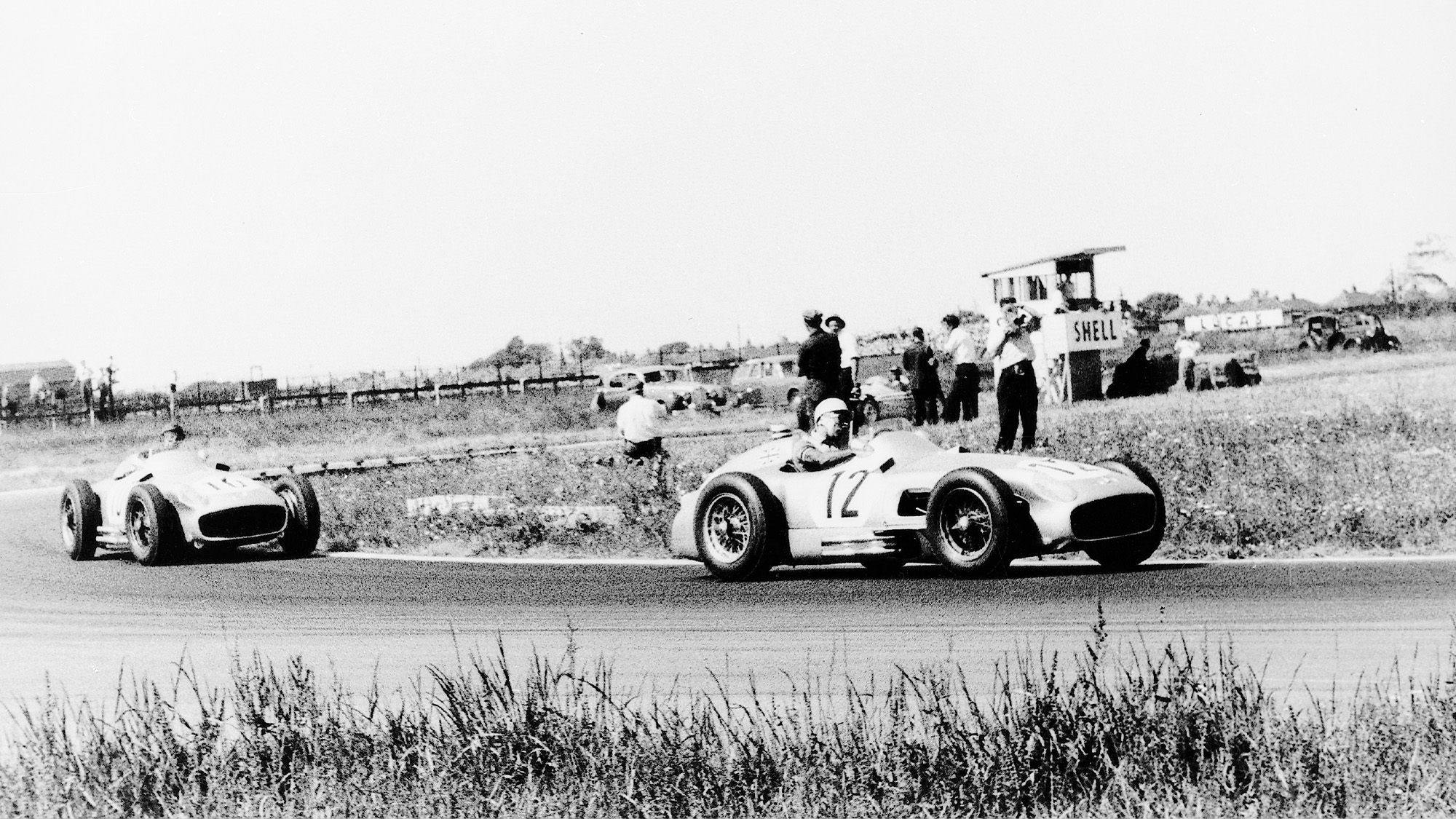 Stirling Moss leads Juan Manuel Fangio in Mercedes W196 R cars at the 1955 F1 British Grand Prix at Aintree