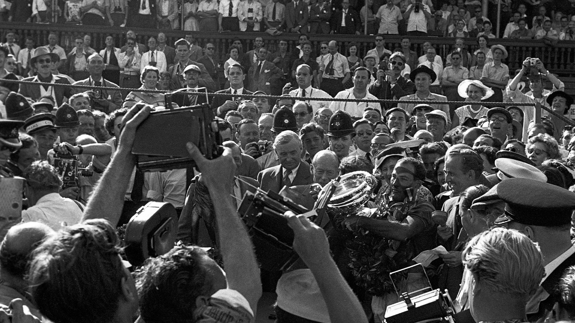 Stirling Moss surrounded by crowds after winning the 1955 British Grand Prix at Aintree